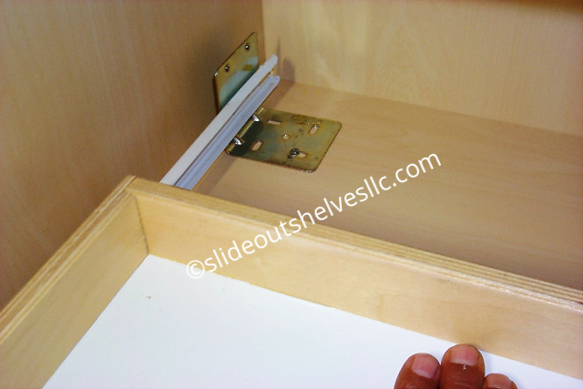 Holding pull out shelf inside kitchen cabinet